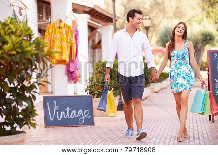 Couple Walking Along Street With Shopping Bags