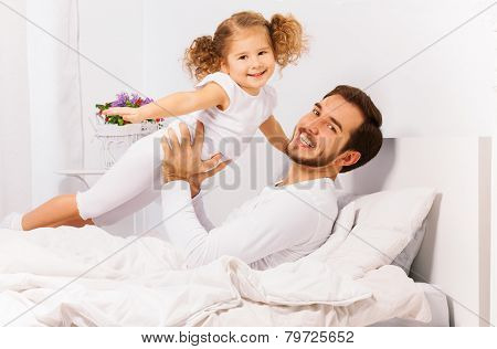 Happy father holds with arms his small daughter