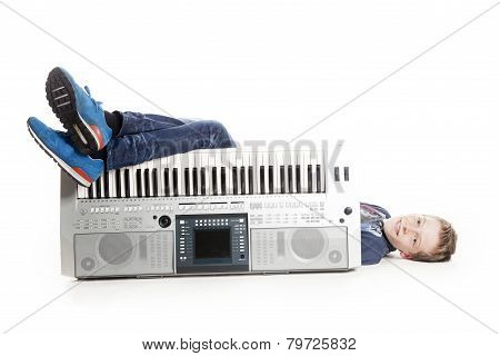 Teenage Boy Lying Behind Keyboard In Studio