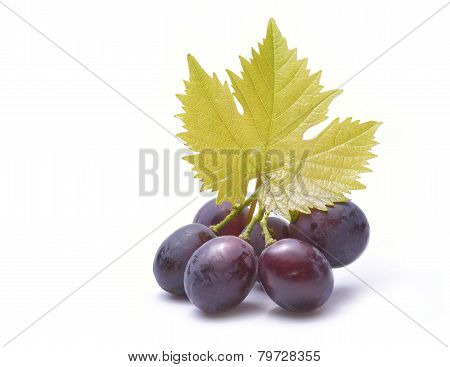Red Grapes With Leaves Isolated On White