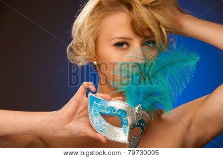 Beauty Portrait Of Beautiful Young Blonde Woman With Venice Carnival Mask In Hands Over Blue Backgro