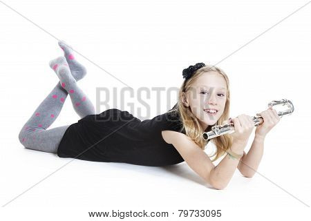 Young Blond Girl Holds Flute Lying Down In Studio