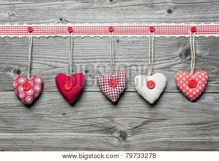 Red hearts hanging over old wood background. Valentine's Day background