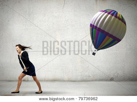 Young businesswoman pulling colorful aerostat with rope