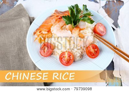 Boiled rice with shrimps, salmon and tomatoes on plate and space for your text