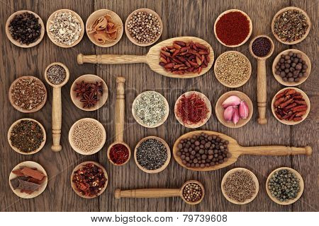 Spice and herb selection in wooden bowls and spoons over old oak wood background.