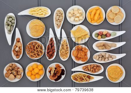 Large savoury snack selection in porcelain dishes over grey wooden background.