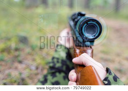 hunting, war, army, technology and people concept - close up of young soldier or sniper hands holding gun with virtual screen projection and aiming in forest
