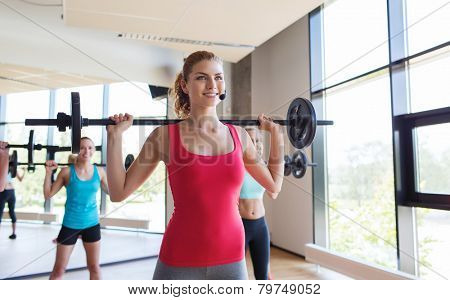 fitness, sport, training, gym and lifestyle concept - group of women excercising with bars in gym