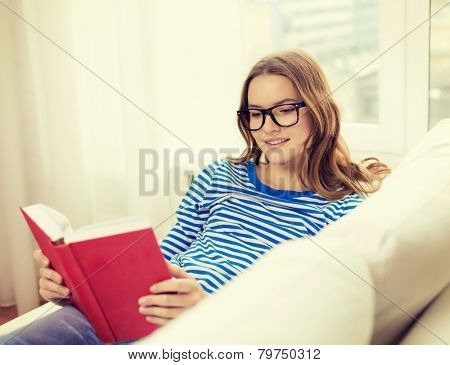leisure, education and home concept - smiling teenage girl in glasses reading book and sitting on couch at home