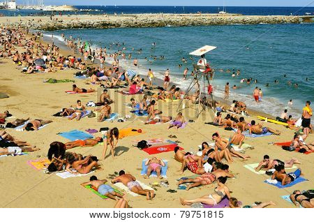 BARCELONA, SPAIN - AUGUST 19: A crowd of bathers in La Barceloneta Beach on August 19 2014 in Barcelona, Spain. This popular beach hosts about 500,000 visitors from everywhere during the summer season