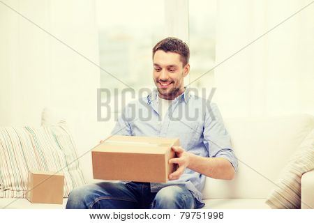 post, home and lifestyle concept - smiling man with cardboard boxes at home