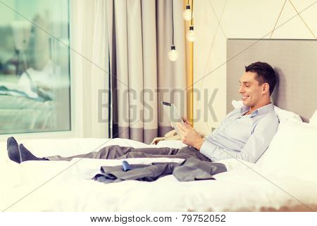 business, technology, internet and hotel concept - happy businessman with tablet pc computer lying in hotel in bed