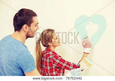 repair, building and home concept - smiling couple painting small heart on wall at home