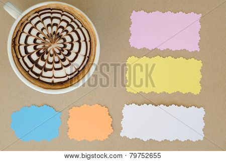 A Cup Of Latte Art And Note Paper On Brown Paper Background