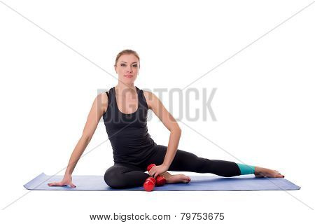 Cute trainer posing on fitness mat with dumbbells
