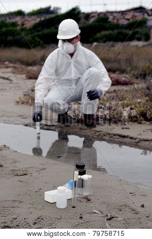 Technical in a protective suit examining pollution