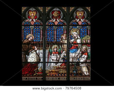 VIENNA, AUSTRIA - OCTOBER 11: Virgin Mary with baby Jesus, angels and Saints, Stained glass in Votiv Kirche (The Votive Church). It is a neo-Gothic church in Vienna, Austria on October 11, 2014