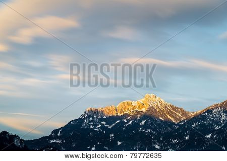 afterglow on austrian mountains with motion clouds in winter