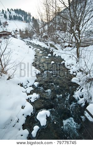 View of frozen river countryside. Brook in snowy landscape. Romanian small river in winter scenery