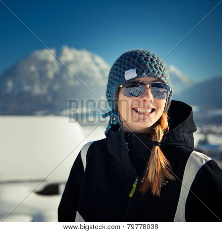 young girl with cap and sunglasses standing in winter scenery
