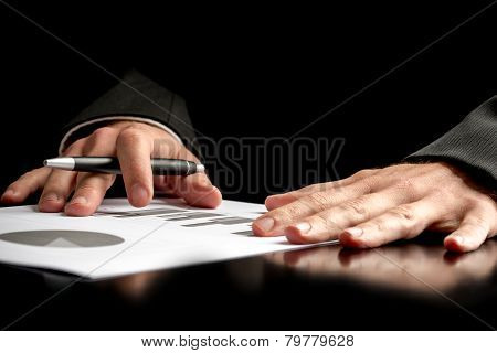 Businessman Analysing A Set Of Graphs Over Black Background