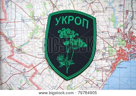 Kiev,Ukraine.JAN 10.Illustrative editorial.Unformal chevron of Ukrainian Army.With map of Mariupol. City and port on Azov Sea.At present time frontline. At January 10,2015 in Kiev, Ukraine