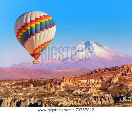Balloon flying over rock landscape at Cappadocia Turkey with Erciyes Mountain.