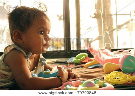 Indian baby playing with toys on bed against the window