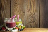 image of smoothies  - Measuring tape around three flavored detox smoothies in jars with space for text - JPG