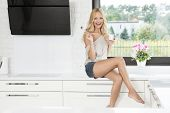picture of natural blonde  - blond beautiful girl in short sitting near the window in a white kitchen  - JPG