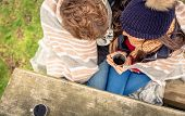 stock photo of hot couple  - View from above of young couple under striped blanket having hot beverage outdoors in a cold day