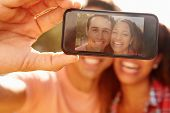 stock photo of two women taking cell phone  - Couple On Holiday Taking Selfie With Mobile Phone - JPG