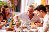 picture of multi-generation  - Multi Generation Family Eating Meal At Outdoor Restaurant - JPG