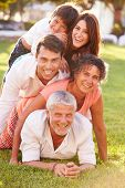 pic of piles  - Multi Generation Family Lying In Pile Up On Grass Together - JPG