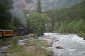 stock photo of chug  - One of the last steam trains in America steaming along by the Animas river - JPG