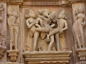 foto of kandariya mahadeva temple  - Sculptures of loving couples illustrating the Kama Sutra on walls of Kandariya Mahadeva Temple at Khajuraho in India Asia - JPG