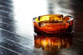 stock photo of box-end  - Glass ashtray on wooden table  - JPG