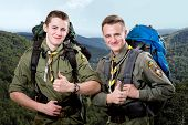 foto of sleeping bag  - Two young scout boys with sleeping bag and backpack traveling in the mountains - JPG