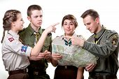 stock photo of boy scouts  - Four young scout members in uniform looking to the map and compass isolated on white background - JPG