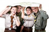 foto of boy scouts  - Four young scout members in uniform with map isolated on white background - JPG