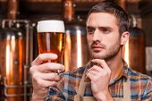foto of apron  - Thoughtful young male brewer in apron holding glass with beer and looking at it while standing in front of metal containers - JPG