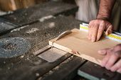 stock photo of sawing  - Carpenter working with oak wood on the circular saw - JPG