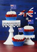 stock photo of red velvet cake  - Happy Australia Day January 26 party food with red velvet cupcakes with kangaroo flag on dark red and blue vintage rustic recycled wood background - JPG