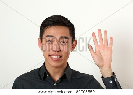 Smiling young Asian man giving the stop sign and looking at camera.