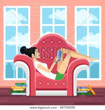 Cute young woman in chair reading book