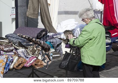 Woman Looks At Fabric On Market Stall In The Netherlands