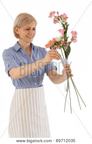 Happy florist making a bouquet of flowers.
