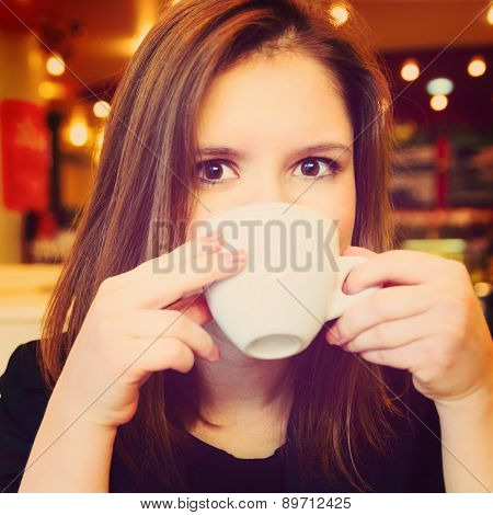 young woman is drinking in modern cafe