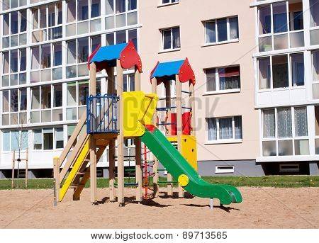 Colorful children playground in nature, front of row newly built block flats
